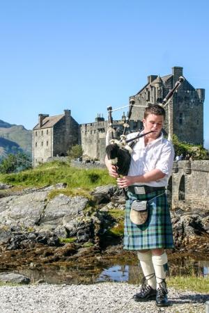 Bagpiper, Eileen Donan Castle in Dornie with Loch Duich, Scotlan