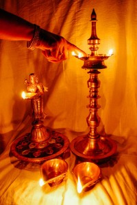 """""""Lighting the lamps"""" This is a very ancient tradition in India. For generations lamps are lit in the house. The types of lamps vary from household to household and in the olden days the grander the lamps the grander the status of the house. The flame in the lamp is equated to the lighting of the soul. The lamp that is being lit is called the 'Kuthu Villake' and has five corners, each representing the five elements. This is one of the most common lamps and you will find it in most houses. The lamp to the left is the 'Paavai Villake' or the lady lamp. It is a beautifully carved lamp with a very ornate base. The lamps are lit with oil and a thread called the 'Thiri'. The thiri is soaked in the oil and then lit."""